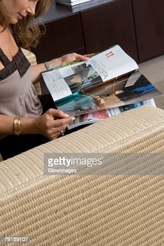 Side profile of a mature woman sitting in an armchair and reading a magazine : Foto de stock