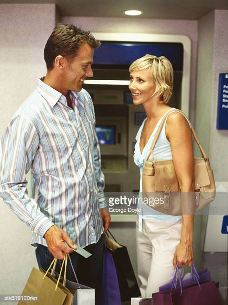 side profile of a mid adult couple holding shopping bags