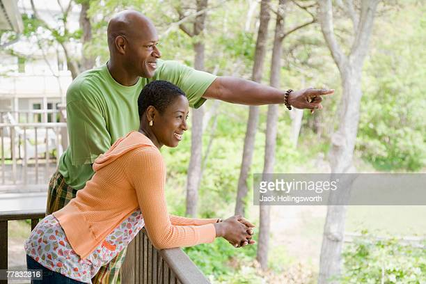 Side profile of a mid adult couple standing at a balcony and smiling
