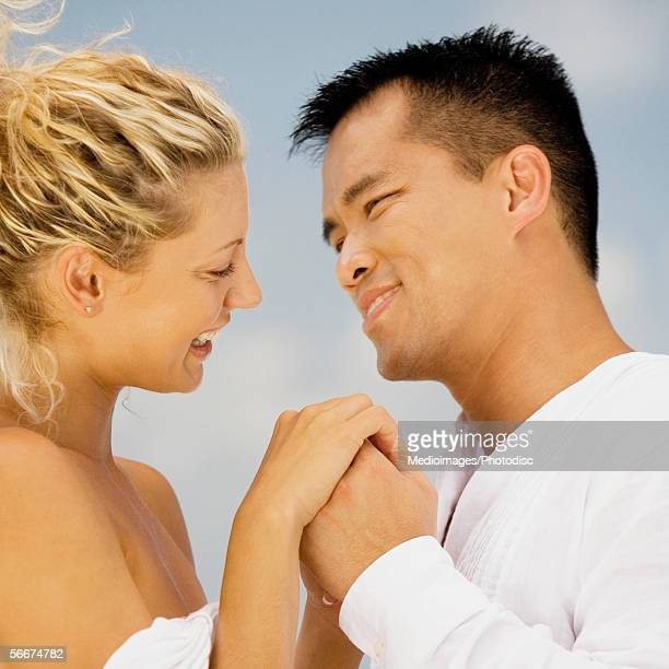 Side profile of a mid adult man and a young woman holding hands on the beach