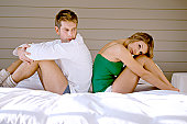 Side profile of a mid adult man and a young woman sitting back to back on the bed