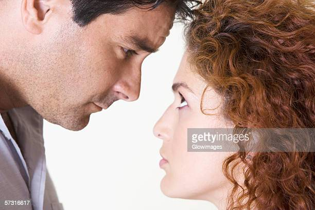 Side profile of a mid adult man and a young woman staring at each other