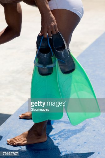 Side profile of a mid adult man holding a pair of flippers : Stock Photo