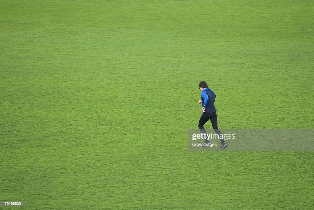 Side profile of a mid adult man running in a field : Foto de stock