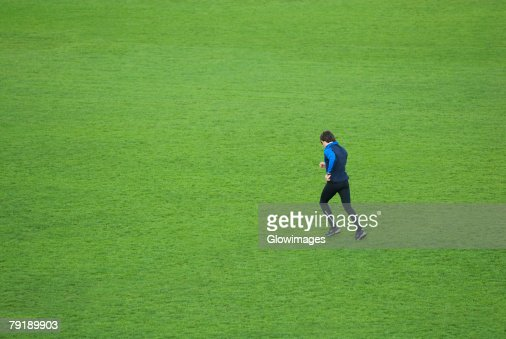 Side profile of a mid adult man running in a field : Foto de stock