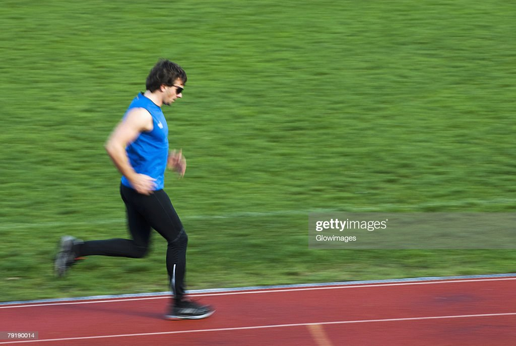 Side profile of a mid adult man running on a sports track : Foto de stock