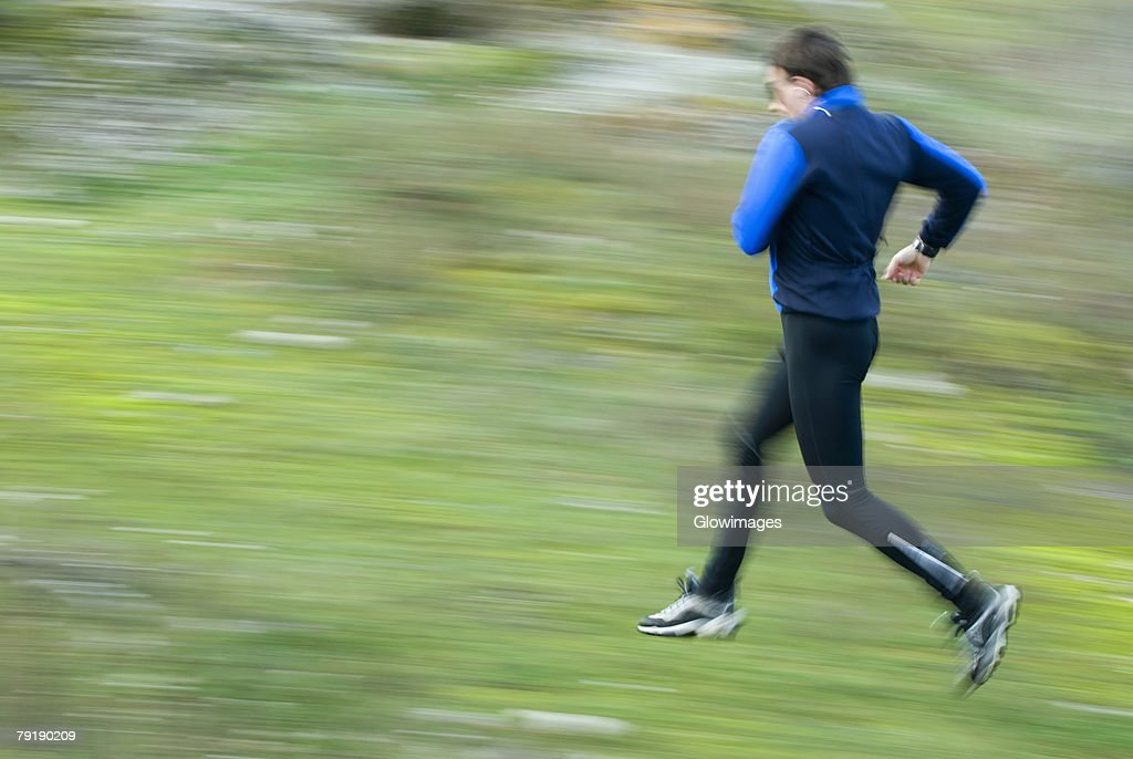 Side profile of a mid adult man running : Foto de stock