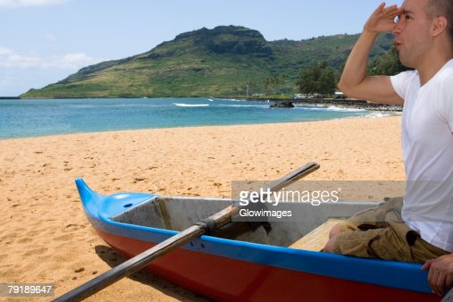 Side profile of a mid adult man sitting in a boat and shielding his eyes on the beach, Nawiliwili Beach Park, Kauai, Hawaii Islands, USA : Stock Photo