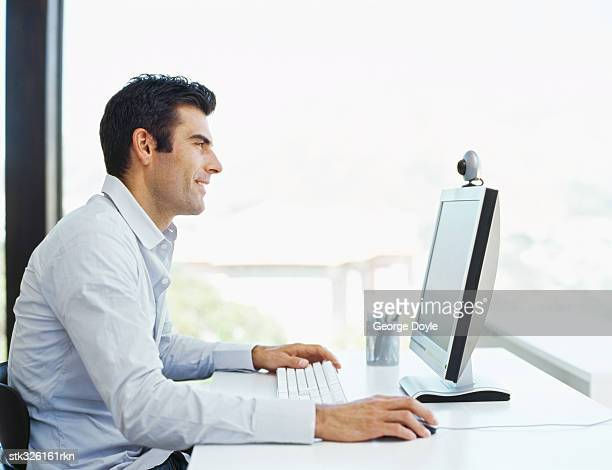 side profile of a mid adult man using a computer