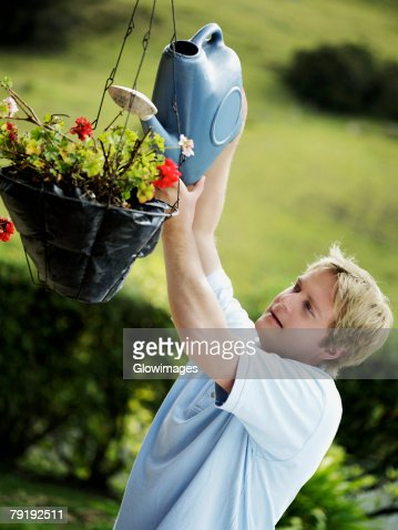 Side profile of a mid adult man watering a potted plant : Foto de stock