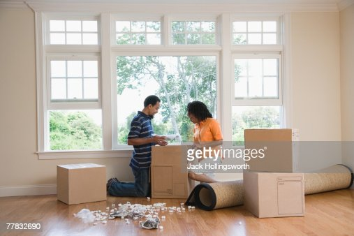 Side profile of a mid adult woman and a young man looking in a cardboard box