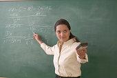 Side profile of a mid adult woman explaining on a blackboard