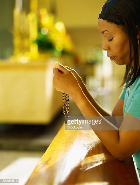 side profile of a mid adult woman holding rosary beads in church