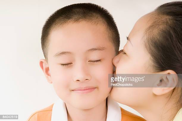 Side profile of a mid adult woman kissing her son