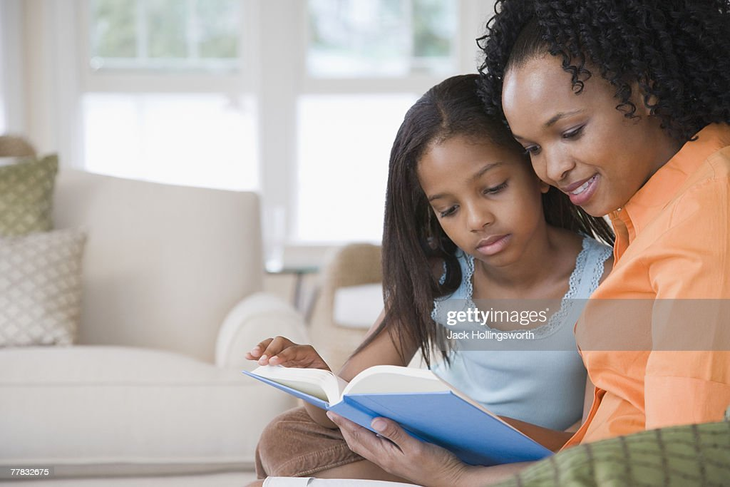 Side profile of a mid adult woman reading a book with her daughter and smiling : Stockfoto