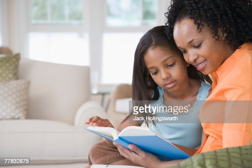 Side profile of a mid adult woman reading a book with her daughter and smiling : Bildbanksbilder