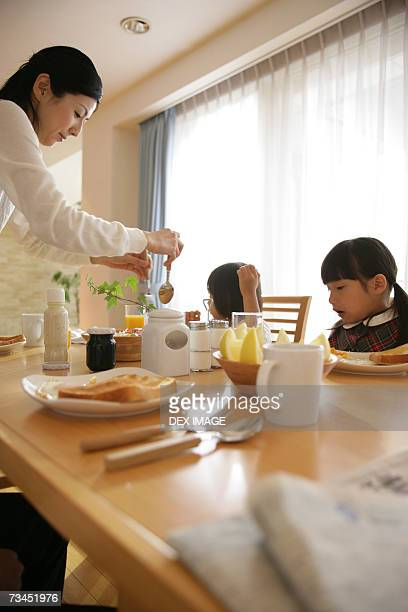 Side profile of a mid adult woman serving her daughters breakfast