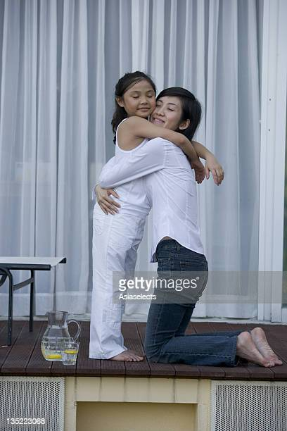 Side profile of a mother and her daughter hugging each other