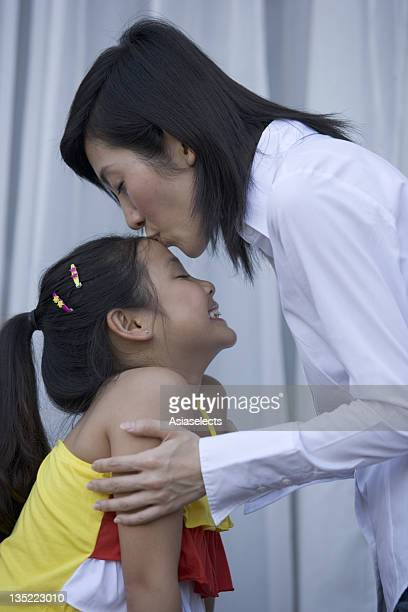 Side profile of a mother kissing her daughter's forehead