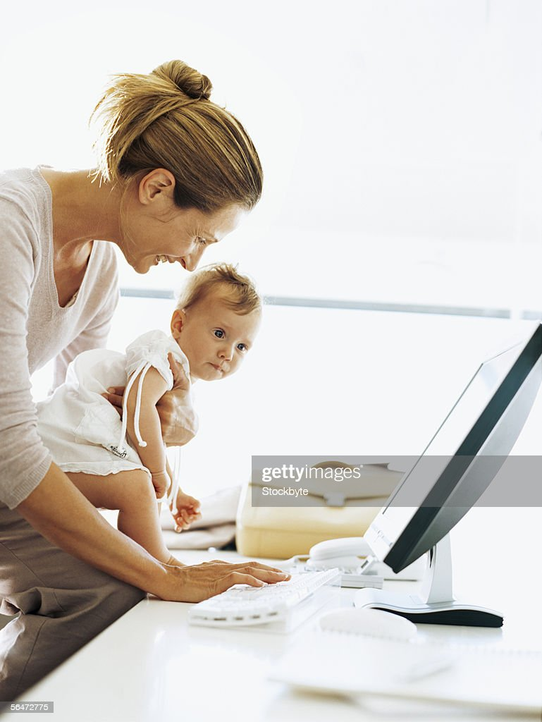 side profile of a mother working on a computer with her daughter in her hands : Stock Photo