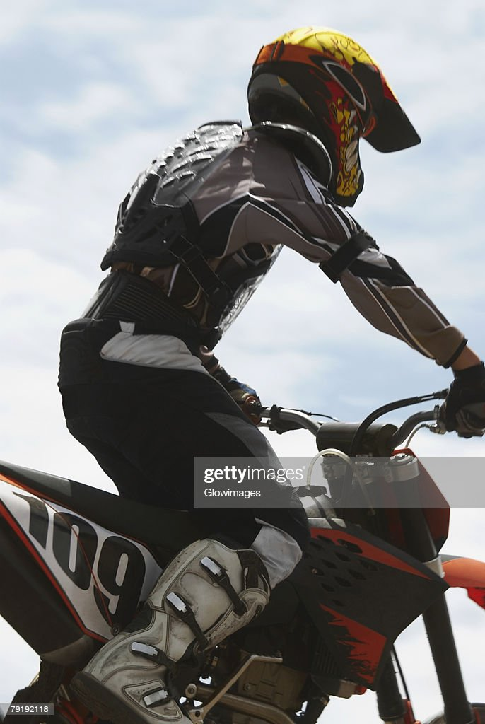 Side profile of a motocross rider riding a motorcycle : Stock Photo