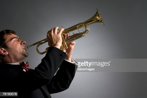 Side profile of a musician playing a trumpet : Stock Photo