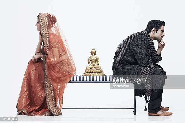Side profile of a newlywed couple sitting on opposite ends of a bench with a statue of Buddha between them