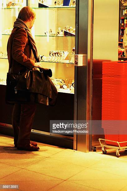 Side profile of a passenger looking at store window