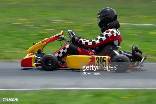 Side profile of a person go-carting on a motor racing track : Foto de stock