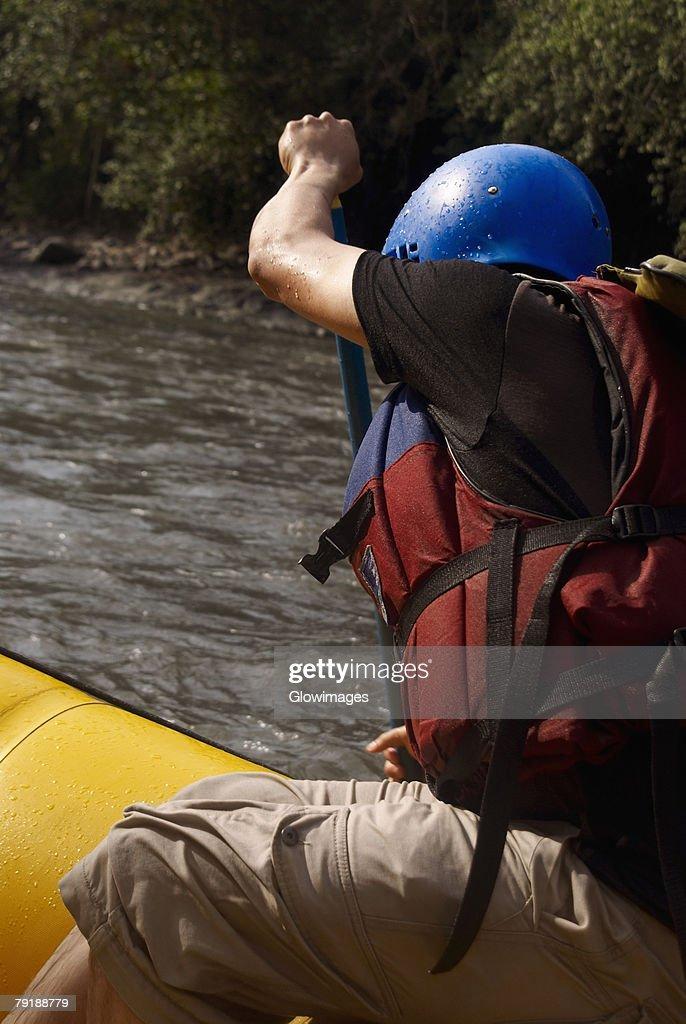 Side profile of a person rafting in a river : Foto de stock