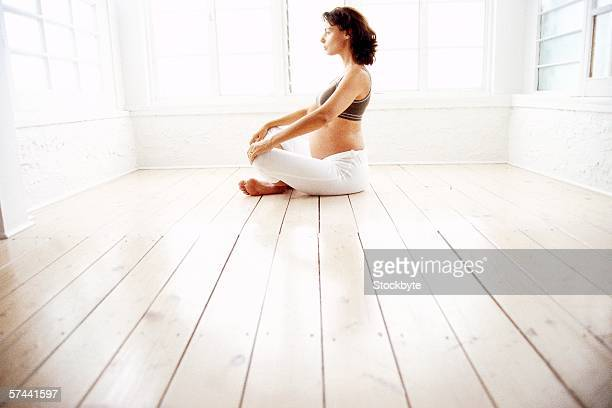 side profile of a pregnant woman sitting in a meditative pose