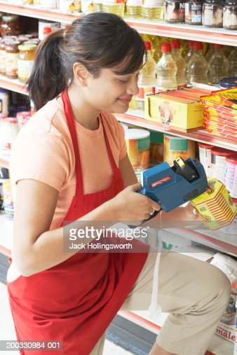 Side profile of a saleswoman decoding the price of a grocery item with a bar code reader