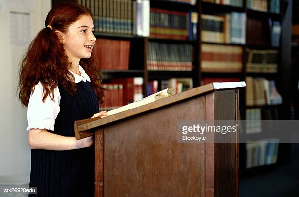 side profile of a school girl (8-10) reading from a podium in the library