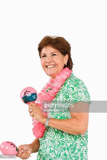 Side profile of a senior woman playing maracas and smiling