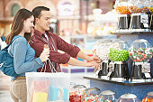 Side profile of a teenage couple taking candy in a candy store
