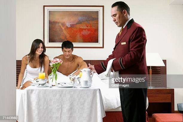 Side profile of a waiter serving a young woman and a mid adult man breakfast in bed