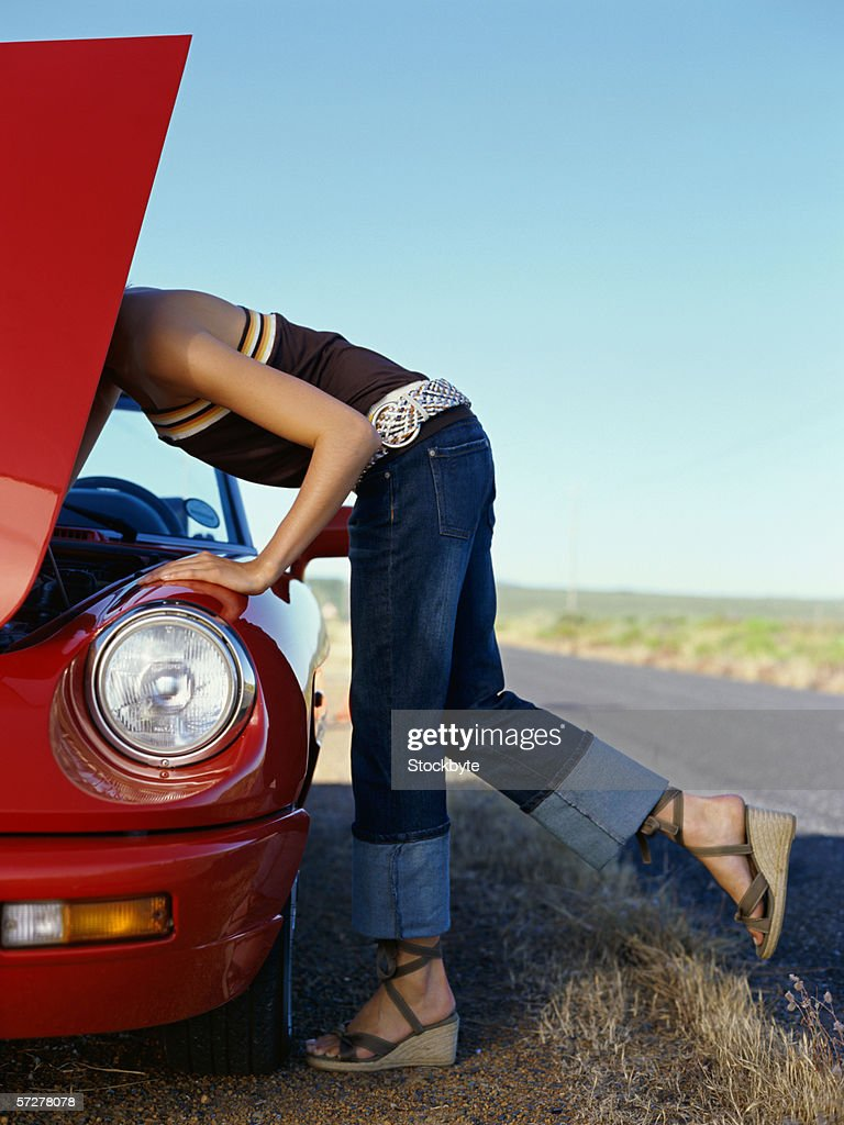 Side profile of a woman bending over a car engine : Stock Photo