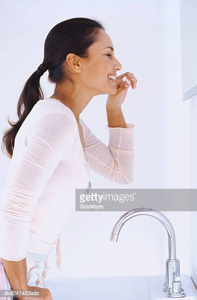 Side profile of a woman brushing her teeth