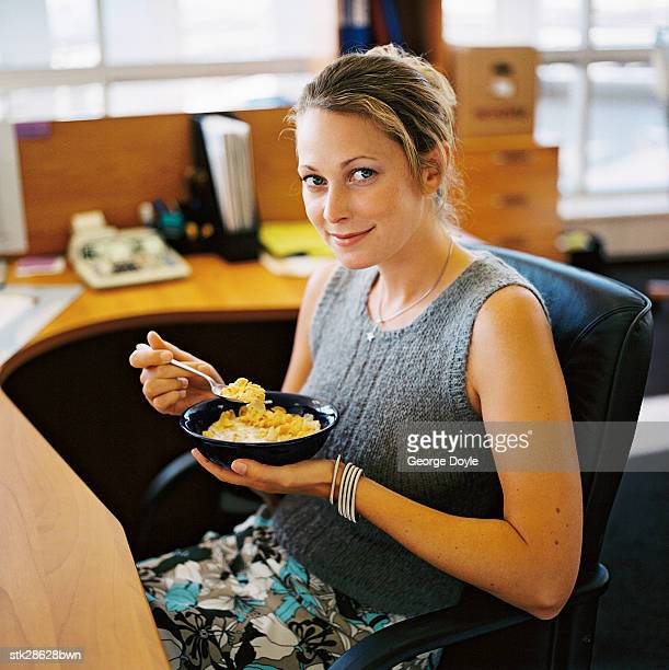 side profile of a woman eating from a bowl at work