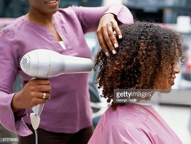 Side profile of a woman having her hair dried with a hair dryer