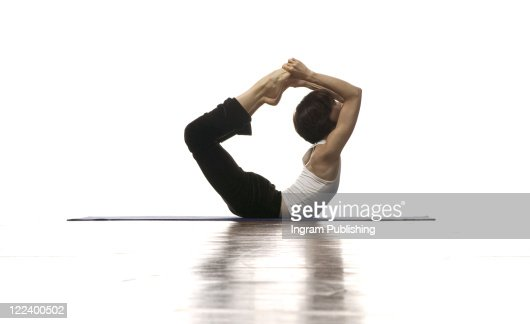 Side profile of a woman performing bow pose : Stock Photo