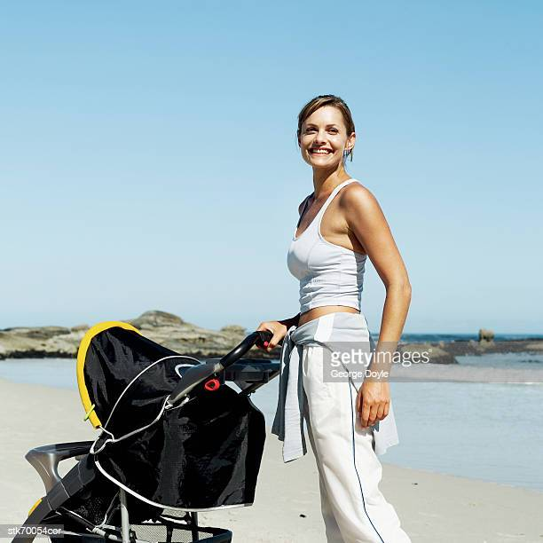 side profile of a woman pushing a stroller on the beach