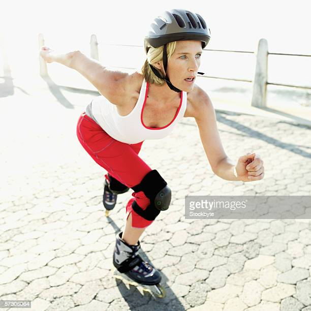 Side profile of a woman rollerblading on a pier