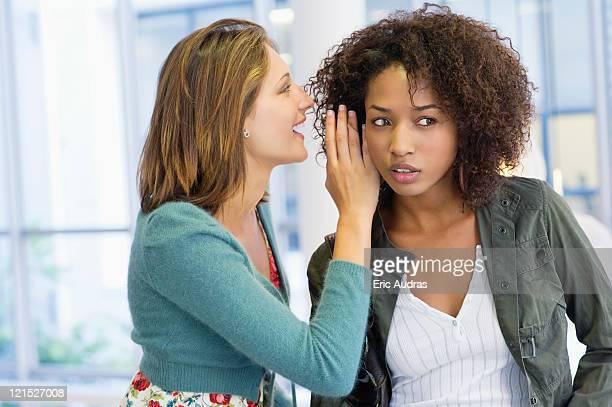 Side profile of a woman whispering in her friend's ear in university