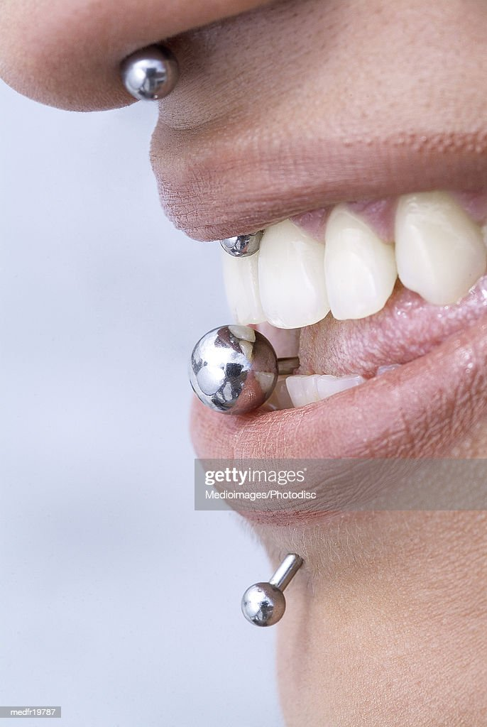 Side profile of a woman's mouth with piercing