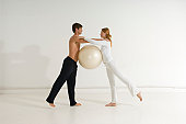 Side profile of a young couple exercising with a fitness ball