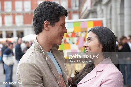 Side profile of a young couple looking at each other : Stock Photo