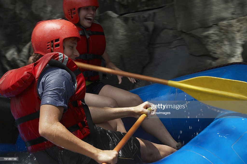 Side profile of a young couple rafting : Stock Photo
