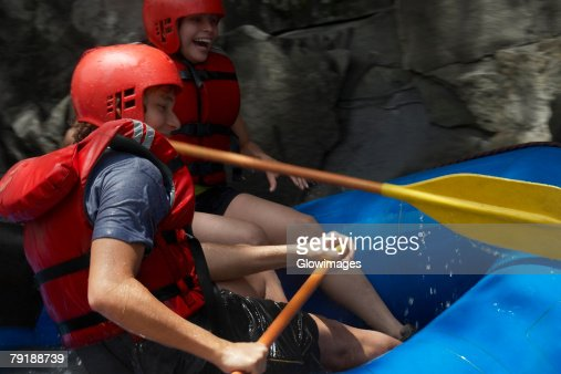 Side profile of a young couple rafting : Foto de stock