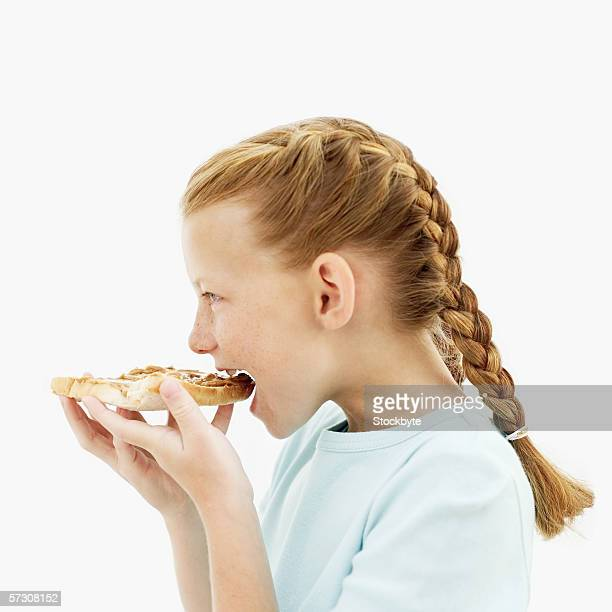 Side profile of a young girl (10-11) eating a slice of bread with peanut butter